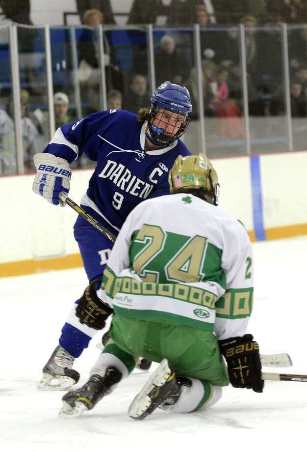 Darien's Dana Wensberg (9) makes a pass as Notre Dame's Eric Austin (24) defends during the boys ice hockey game at the Bennett Ice Rink in West Haven on Wednesday, Jan. 2, 2013. Photo: Amy Mortensen / Connecticut Post Freelance