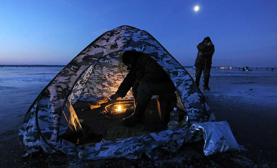 A man sits in a tent while ice fishing at sunrise in the Lake Vileika near the Belarus village of Kasun, some130 km north of the capital Minsk early on January 2, 2013. Photo: Viktor Drachev, AFP/Getty Images