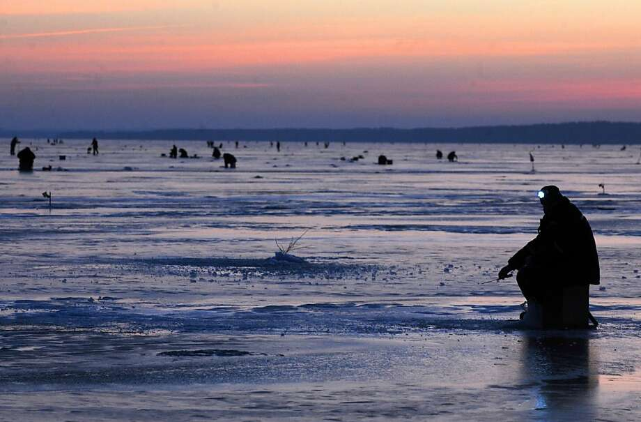 A man (front R) uses a headlamp while ice fishing at sunrise in the Lake Vileika near the Belarus village of Kasun, some130 km north of the capital Minsk early on January 2, 2013. Photo: Viktor Drachev, AFP/Getty Images