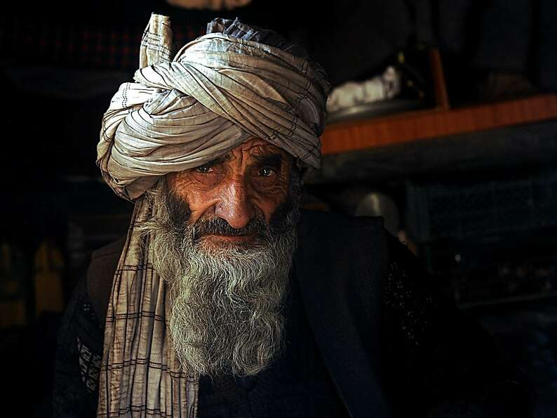 Disembodied head No. 1: An Afghan man sits for a portrait at a refugee camp in Herat.