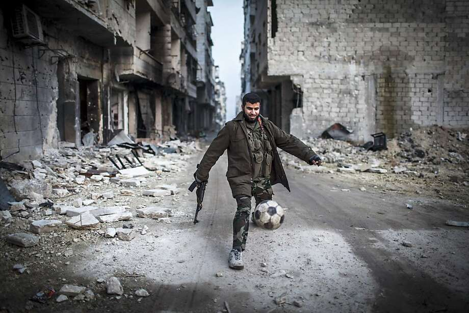 "A Syrian rebel plays football in the Saif al-Dawlah neighborhood of Aleppo, Syria, Wednesday, Jan. 2, 2013. The United Nations estimated Wednesday that more than 60,000 people have been killed in Syria's 21-month-old uprising against authoritarian rule, a toll one-third higher than what anti-regime activists had counted. The U.N. human rights chief called the toll ""truly shocking."" Photo: Andoni Lubaki, Associated Press"