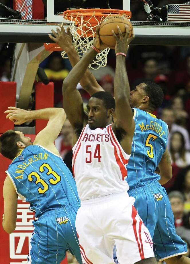 Patrick Patterson overpowers the Hornets' Ryan Anderson (33) and Dominic Mc-Guire during a show of force that included 15 points and 10 rebounds Wednesday. Photo: Nick De La Torre, Staff / © 2013  Houston Chronicle