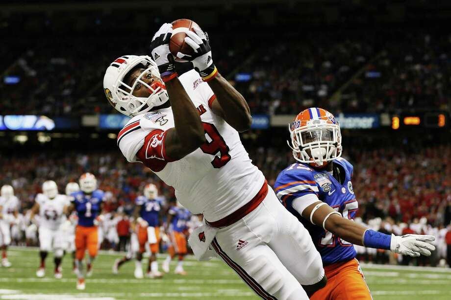 NEW ORLEANS, LA - JANUARY 02:  DeVante Parker #9 of the Louisville Cardinals catches a second quarter touchdown pass over Loucheiz Purifoy #15 of the Florida Gators during the Allstate Sugar Bowl at Mercedes-Benz Superdome on January 2, 2013 in New Orleans, Louisiana.  (Photo by Kevin C. Cox/Getty Images) Photo: Kevin C. Cox