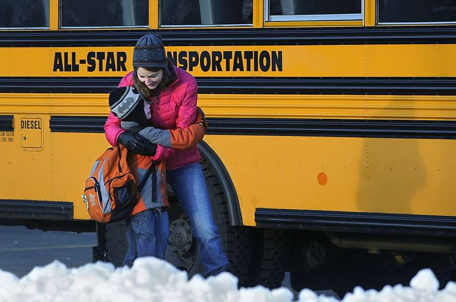 A woman hugs a child before he boards a bus on the first day of classes after the holiday break, in Newtown, Conn., Wednesday, Jan. 2, 2013.    Children from Sandy Hook Elementary School will return to school Thursday in the neighboring town of Monroe. Photo: Jessica Hill, Associated Press