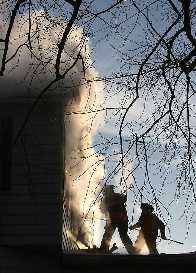 Firefighters working from the roof of a carport use pike poles to pull loose siding and other debris in the early morning light Wednesday Jan. 2, 2013, as smoke billows from the two-story house on fire in Jersey County, Ill.  Firefighters battled temperatures in the teens as well as the fire but no injuries were reported. Photo: John Badman, Associated Press