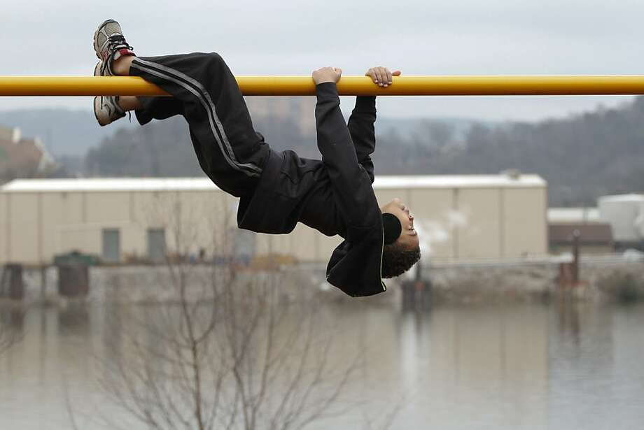 In this photo taken Wednesday, Jan. 2, 2013, Aydian Lyle, 7, performs an inverted crawl across a pole at the PlayCore Riverfront Playground beside the Tennessee River in Chattanooga, Tenn. while spending time outdoors with his family. Photo: Dan Henry, Associated Press