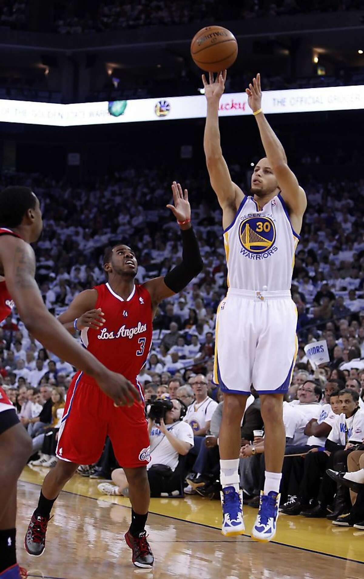 Stephen Curry puts up a three-point shot past Chris Paul in the first half of the game. The Warriors played the Los Angeles Clippers at Oracle Arena in Oakland, Calif., on Wednesday, January 2, 2013.