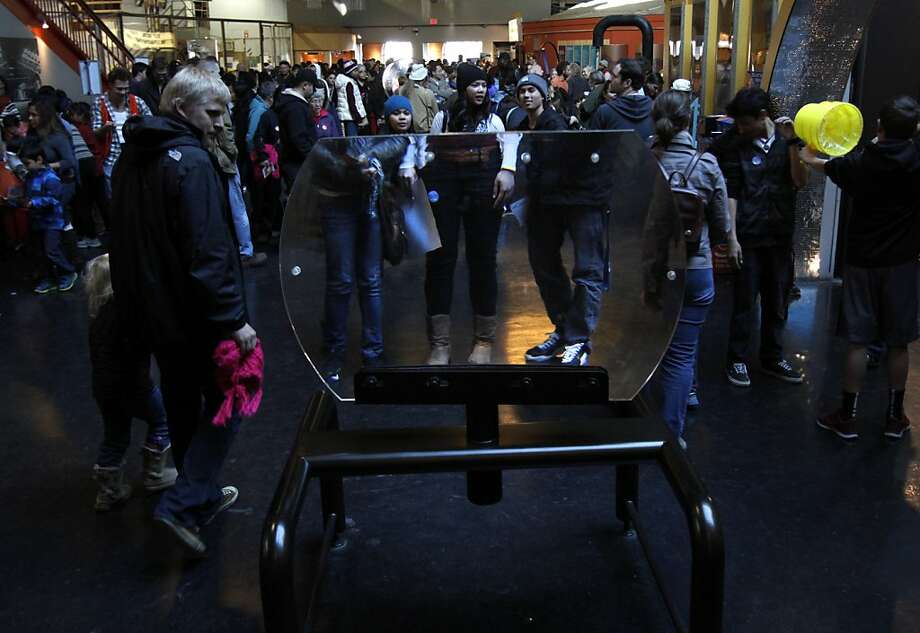 A giant magnifying glass enlarges the appearance of visitors on the last day the Exploratorium is open in San Francisco, Calif., Wednesday, January 2, 2013.  After Wednesday the Exploratorium will be closed while it moves to its new location at Pier 15. Photo: Sarah Rice, Special To The Chronicle