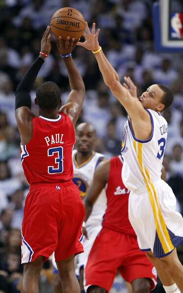 Stephen Curry tries to block a shot by Chris Paul in the first half of the game. The Warriors played