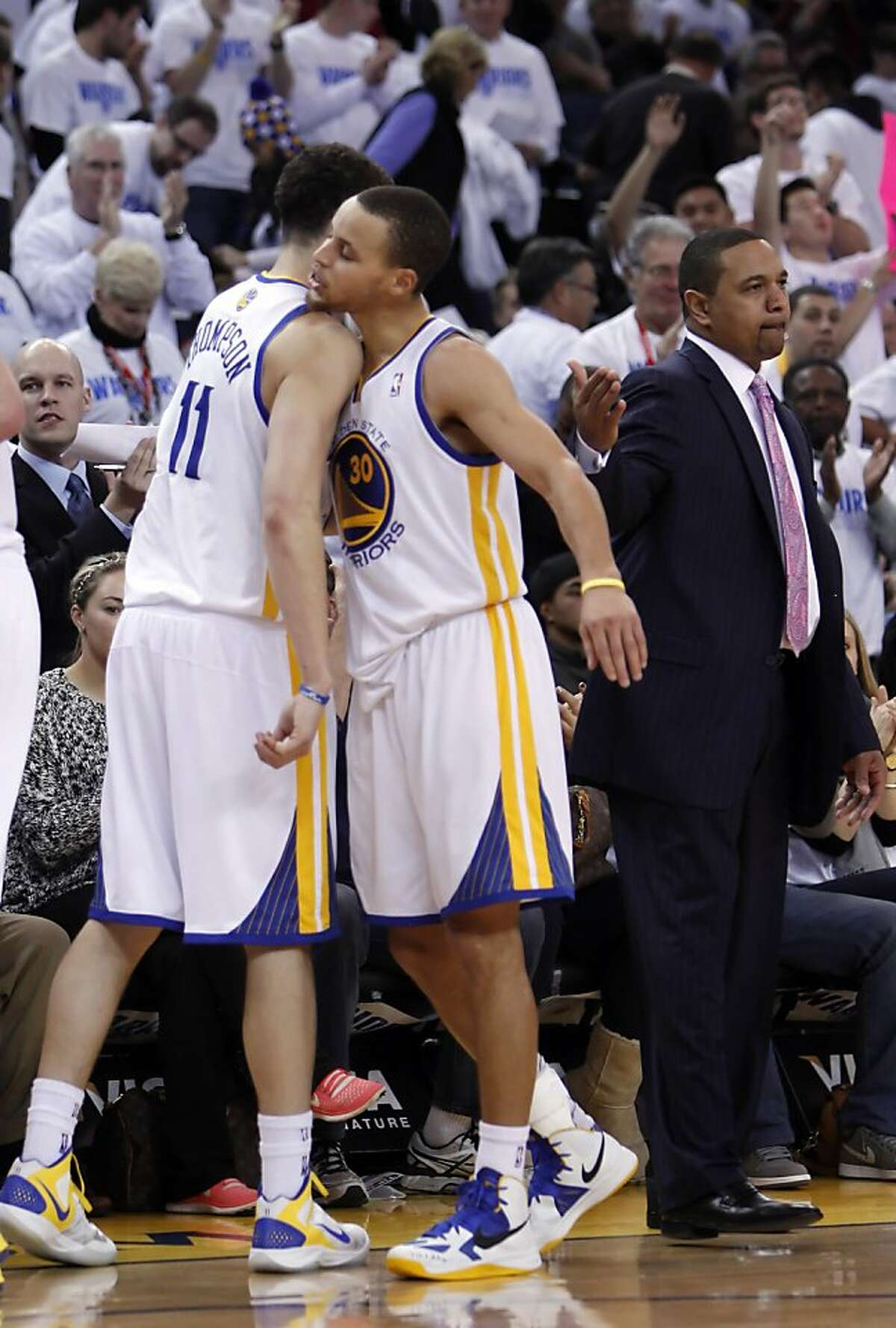Stephen Curry bumps Klay Thompson after being taken out of the game once it was well in hand at the end of the fourth quarter. The Warriors played the Los Angeles Clippers at Oracle Arena in Oakland, Calif., on Wednesday, January 2, 2013, defeating the Clippers 115-94.
