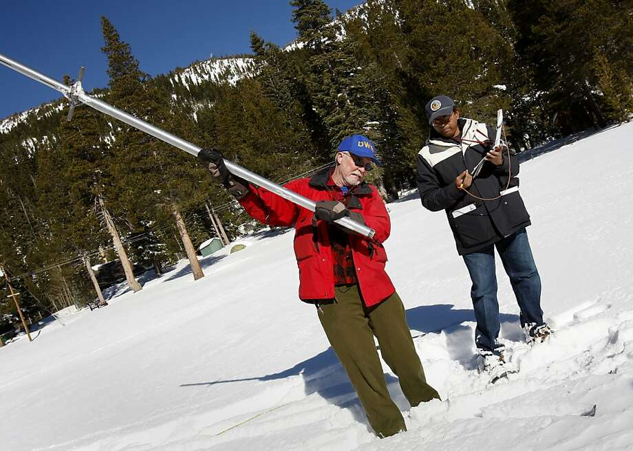 Frank Gehrke (left) of the state survey team clears snow from the depth tube as Sudhakar Talonki (right) watches. The first snow survey of the new year Wednesday January 2, 2013 found slightly above averages of snow and water content in the Phillips, Calif. meadow near Echo Summit. Photo: Brant Ward, The Chronicle