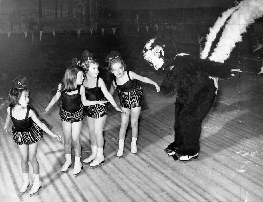 Local children perform with/try to escape from a skunk in the Ice Caprice of 1962. Like every ice skating costume before the 1980s, it was designed to make children never want to step foot near an ice rink again. Photo: Gordon Peters, The Chronicle / ONLINE_YES