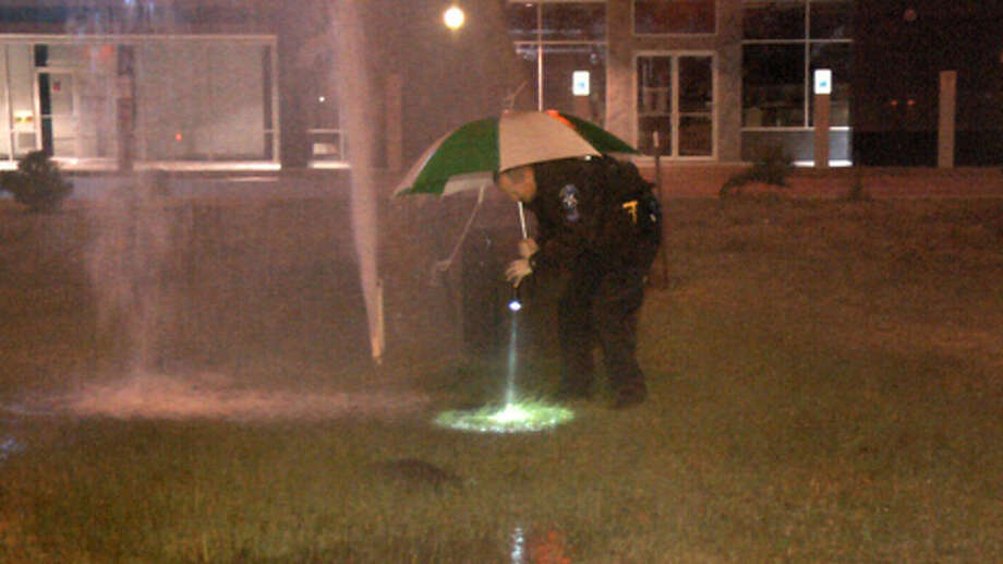 A Shenandoah police officer works quickly to shut off water flow around a shopping center hit by metal thieves Thursday morning. (Scott Engle / Montgomery County Police Reporter) Photo: Montgomgery County Police Reporter