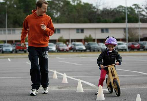 Sofia Kennedy, 4, rides her balance bike under the watchful eye of her father Galvin Kennedy in a parking lot in the Garden Oaks neighborhood Sunday, Dec. 30, 2012, in Houston. 