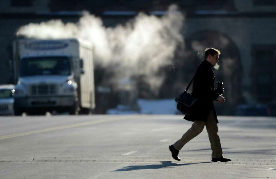With the extreme cold showing the exhaust on a vehicle in the background a man crosses Washington Avenue Tuesday morning Jan. 3, 2013, in Albany, N.Y.   (Skip Dickstein/Times Union) Photo: SKIP DICKSTEIN