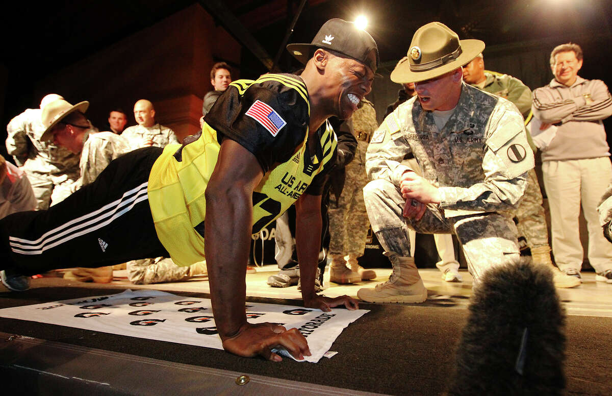Antwuan Davis (left) from Bastrop, Texas grimaces as he performs push-ups with encouragment from drill sergeant leader Christopher Offringa as part the first-ever All-American Soldier-Hero Challenge at Sunset Station on Wednesday, Jan. 2, 2013. Players, band members and soldiers teamed up to compete in sit-ups, push-ups and an eating contest as part of one of many events leading up to Saturday's U.S. Army All-American Bowl game which highlights some of the best high school football players in the country.