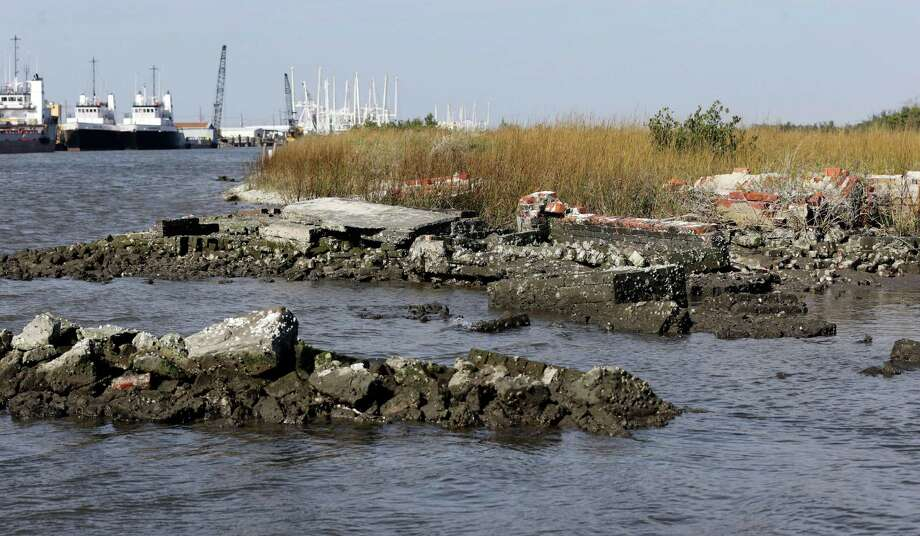 In this Dec. 29, 2012 photo, water washes around the tombs of those buried in a Leeville, La., cemetery. What's left of the old Leeville cemetery is only accessible by boat. Some headstones are barely visible above the water, and waves lap at the bricks and concrete surrounding caskets buried at the site since the late 1800s. Much of the ground has subsided to barely sea level, and during Hurricane Isaac, about seven feet of land washed away in the tidal surge. Photo: Dave Martin, AP / AP