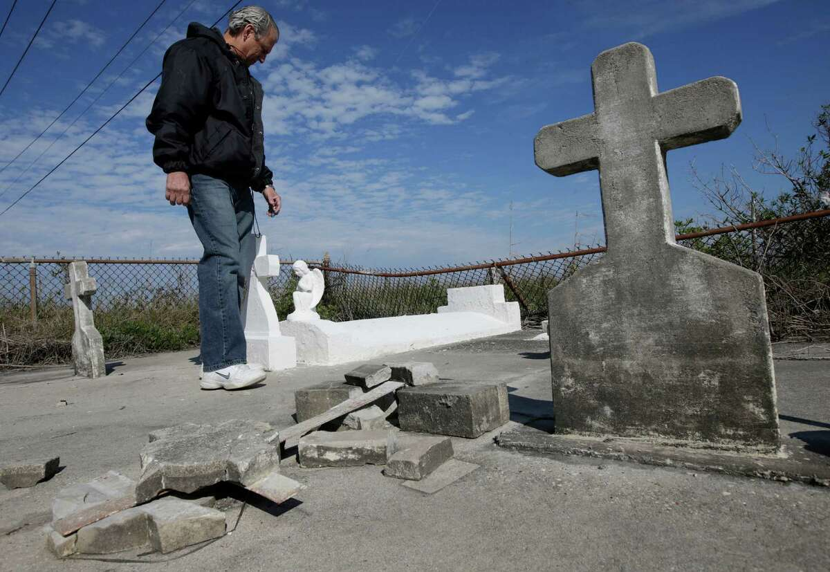 In this Dec. 29, 2012 photo, South Lafourche Levee District General Manager Windell Curole, who also serves on the state's Coastal Protection and Restoration Authority, walks through his small family cemetery which sits along the bayou near Leeville, La. Some 11 cemeteries in Jefferson Parish have repeatedly flooded since Katrina, and in Lafourche, Terrebonne and Plaquemines parishes, more than a dozen others have succumbed to tidal surges. Curole said saltwater from the Gulf is causing a crippling subsidence problem.