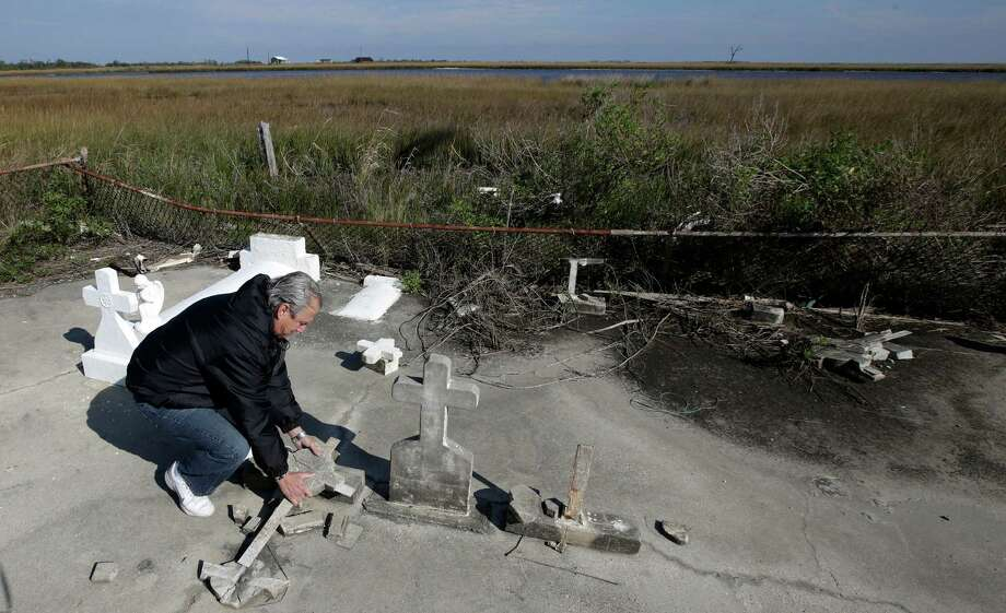 In this Dec. 29, 2012 photo, South Lafourche Levee District General Manager Windell Curole, who also serves on the state's Coastal Protection and Restoration Authority, handles pieces of headstone at his small family cemetery which sits along the bayou near Leeville, La. Some 11 cemeteries in Jefferson Parish have repeatedly flooded since Katrina, and in Lafourche, Terrebonne and Plaquemines parishes, more than a dozen others have succumbed to tidal surges. Curole said saltwater from the Gulf is causing a crippling subsidence problem. Photo: Dave Martin, AP / AP