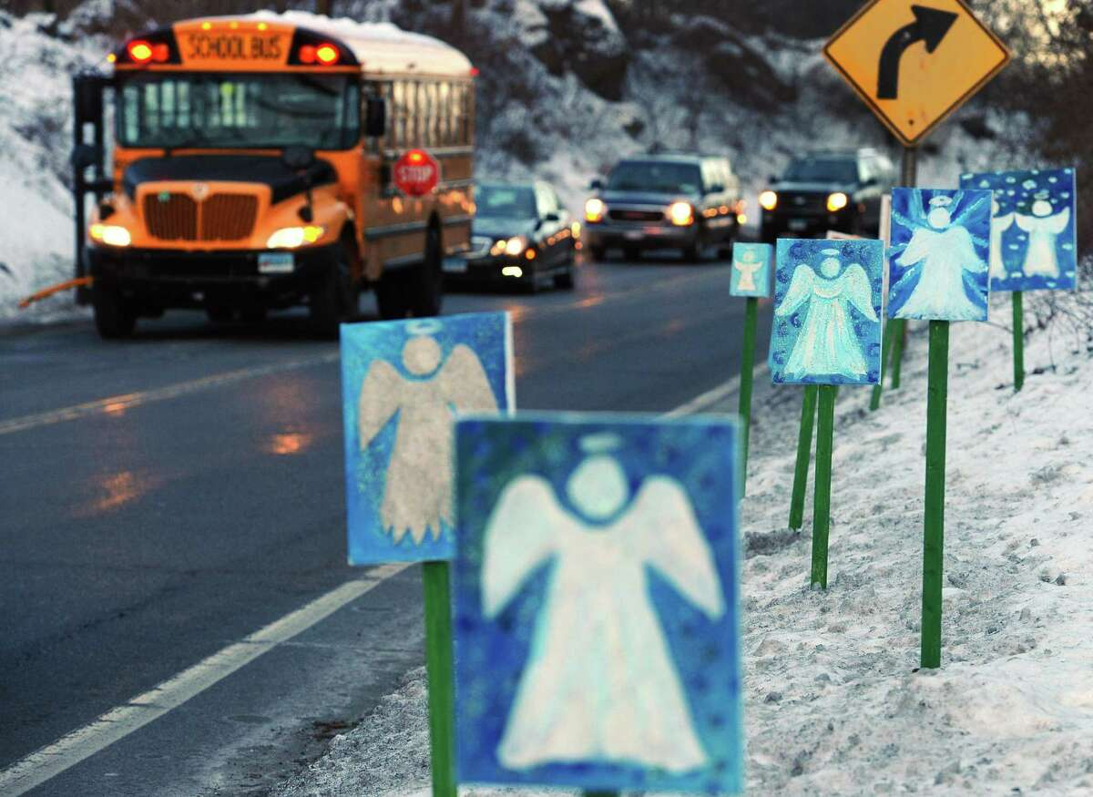A bus traveling from Newtown, Conn., to Monroe stops in front of 26 angels along the roadside on the first day of classes for Sandy Hook Elementary School students since the Dec. 14 shooting, in Monroe, Conn., Thursday, Jan. 3, 2013. Chalk Hill School in Monroe was overhauled especially for the students from the Sandy Hook School shooting.
