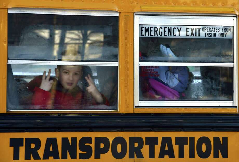 "A Sandy Hook Elementry student flashes a sign as children leave on a school bus  in Newtown , Connecticut January 3, 2013.  Students at the elementary school where a gunman massacred 26 children and teachers last month were returning Thursday to classes at an alternative campus described by police as ""the safest school in America."" Survivors were finally to start their new academic year in the nearby town of Monroe, where a disused middle school has been converted and renamed from its original Chalk Hill to Sandy Hook. AFP PHOTO / TIMOTHY A. CLARYTIMOTHY A. CLARY/AFP/Getty Images Photo: TIMOTHY A. CLARY, AFP/Getty Images / AFP"