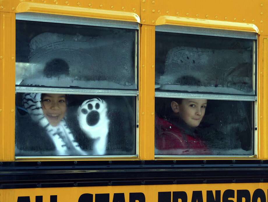 "Sandy Hook Elementry students leave on a school bus  in Newtown, Connecticut on January 3, 2013.  Students at the elementary school where a gunman massacred 26 children and teachers last month were returning Thursday to classes at an alternative campus described by police as ""the safest school in America."" Survivors were finally to start their new academic year in the nearby town of Monroe, where a disused middle school has been converted and renamed from its original Chalk Hill to Sandy Hook. AFP PHOTO / TIMOTHY A. CLARYTIMOTHY A. CLARY/AFP/Getty Images Photo: TIMOTHY A. CLARY, AFP/Getty Images / AFP"