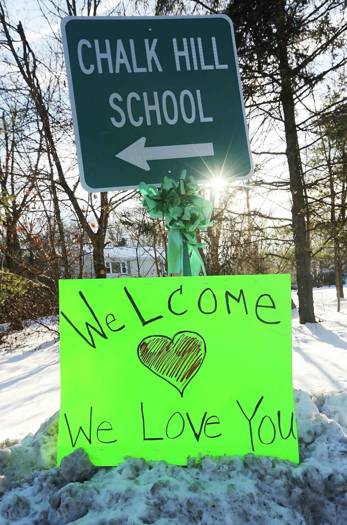 MONROE, CT - JANUARY 03: A sign reads 'Welcome We Love You' beneath a sign pointing to the location of Chalk Hill School, which has been refurbished and renamed Sandy Hook Elementary School on January 3, 2013 in Monroe, Connecticut. Sandy Hook students started their first day of classes in the new building following the mass shooting at the old school in Newtown that left 20 students and six faculty members dead.