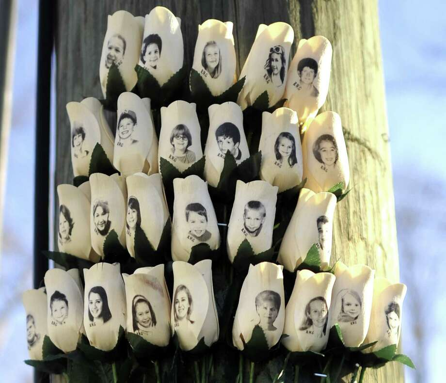 "Roses with the faces of the Sandy Hook Elementry students and adults  killed are seen on a pole in Newtown, Connecticut on January 3, 2013.  Students at the elementary school where a gunman massacred 26 children and teachers last month were returning Thursday to classes at an alternative campus described by police as ""the safest school in America."" Survivors were finally to start their new academic year in the nearby town of Monroe, where a disused middle school has been converted and renamed from its original Chalk Hill to Sandy Hook. AFP PHOTO / TIMOTHY A. CLARYTIMOTHY A. CLARY/AFP/Getty Images Photo: TIMOTHY A. CLARY, AFP/Getty Images / AFP"
