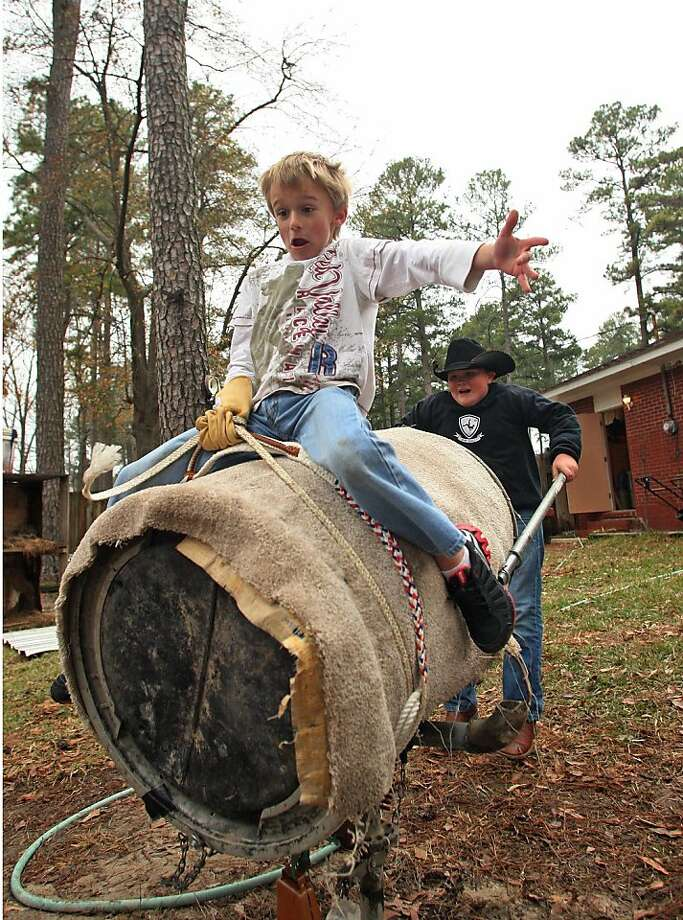 """More fun than a barrel:For Kade Owen to beat the """"mechanical bull"""" outside his home in El Dorado, Ark., he must hang on until brother Hayden's arms give out. Photo: Michael Orrell, Associated Press"""