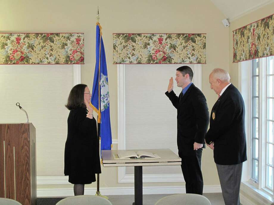 New police officer Christopher Dewey gets sworn in by Town Clerk Claudia Weber. Police Commissioner Jim Cole presides. The ceremony took place Jan. 3, 2013 in the Lapham Community Center in New Canaan, Conn. Photo: Tyler Woods