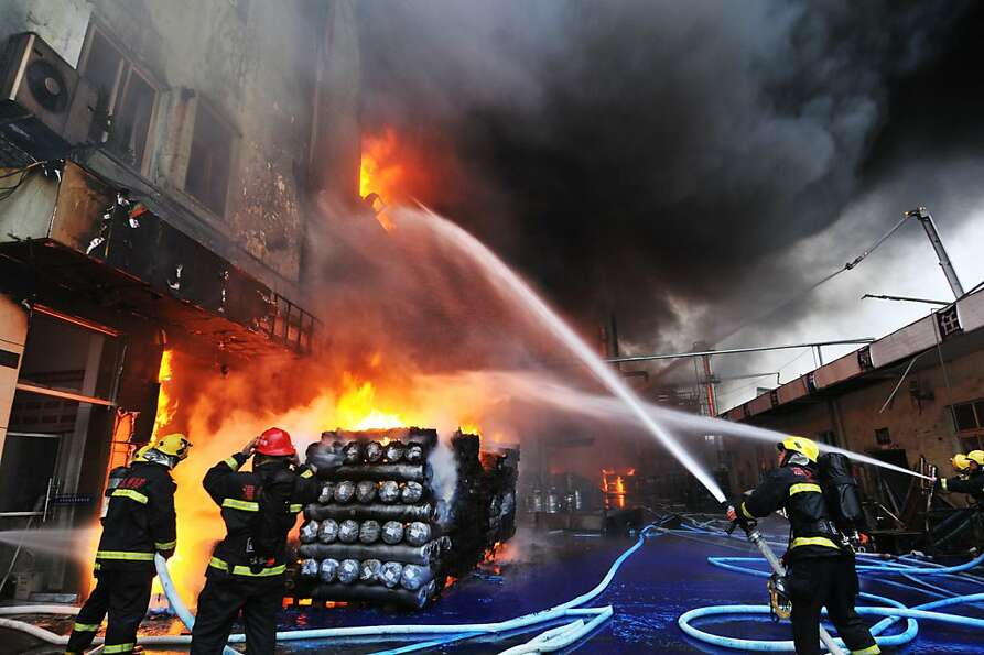 Firefighters battle a blaze at a fur factory that houses six tanks of hazardous chemicals in