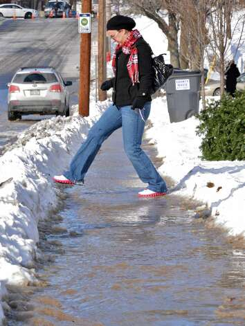 Roulier Heights Apartments resident Sarah Roberts negotiates a flooded sidewalk on her way to work Thursday Jan. 3, 2013, in Cohoes, N.Y.  City officials are dealing with a ruptured water pipe at the Roulier Heights apartments that forced the city to close Garner Street.  (John Carl D'Annibale / Times Union) Photo: John Carl D'Annibale / 00020650A