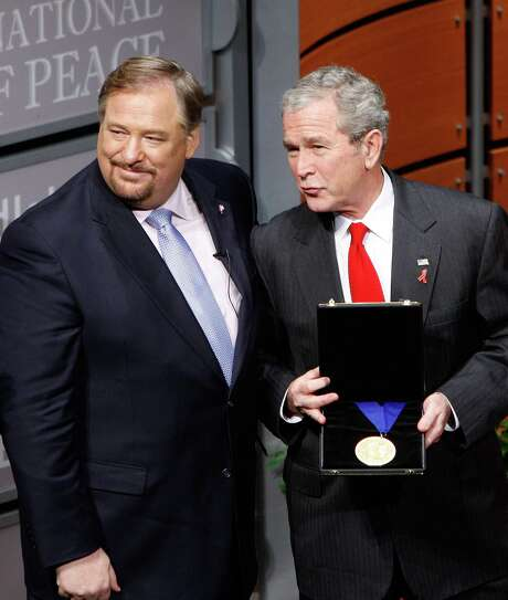 President George W. Bush talks with Dr. Rick Warren, founder of the Saddleback Valley Church, Lake Forest, Calif. after receiving an award from Warren as they participate in the Saddleback Civil Forum on Global Health, Monday, Dec. 1, 2008, at the Newseum in Washington.    (AP Photo/Ron Edmonds) Photo: Ron Edmonds, STF / AP