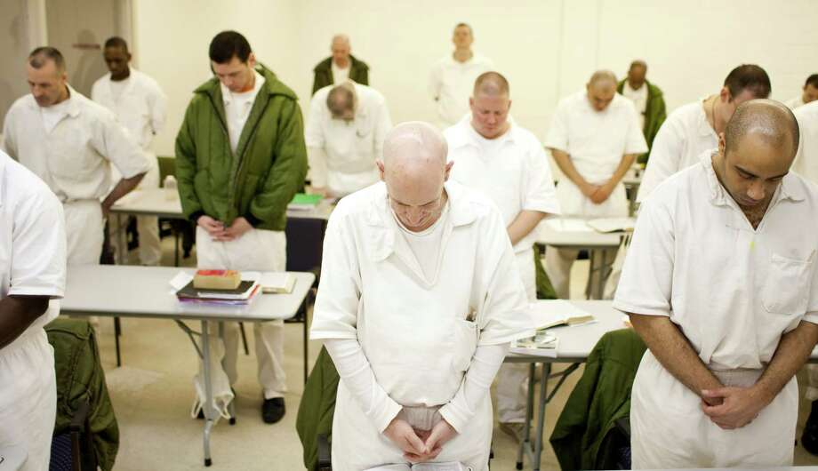 "Marrion Hooper, center, and his seminary classmates pray before breaking for lunch at the Darrington Unit in Rosharon. Hooper, who's serving five life sentences, says the class is ""our way of helping guys in here."" Photo: Nick De La Torre, Staff / © 2011  Houston Chronicle"
