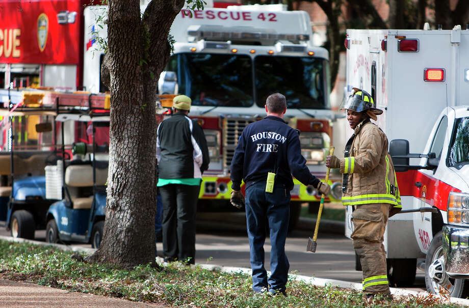 Firefighters leave after rescuing a man from Rice University's Rayzor Hall, Thursday, Jan. 3, 2013, in Houston. Shortly before 11 a.m., the man, an electrician for the university, fell about 10 feet where he landed and was trapped between two air ducts. Photo: Cody Duty, Houston Chronicle / © 2012 Houston Chronicle