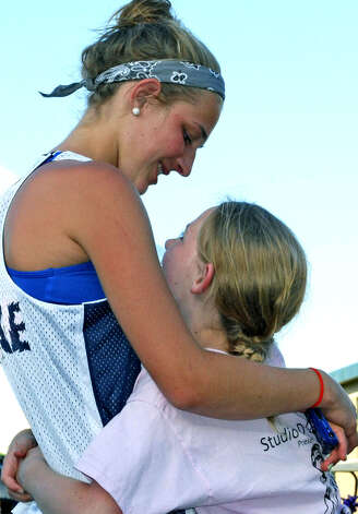 Emily Federowicz, right, and her sister, Lindsey, share a loving hug as they listen to inspirational words during the opening ceremony of the New Milford Relay For Life, a benefit for the American Cancer Society, held in June at Sarah Noble Intermediate School. The girls were there to support the Phys-Ed Relay For Life team. Photo: Deborah Rose