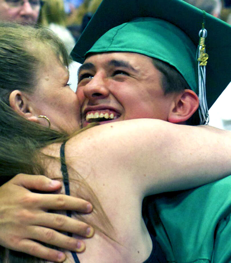 Thomas Bowen lets the emotions flow as he receives a loving hug from his mother, Kelly, moments after the New Milford High School graduation exercises at the O'Neill Center, on the westside campus of Western Connecticut State University in Danbury in June. Photo: Trish Haldin