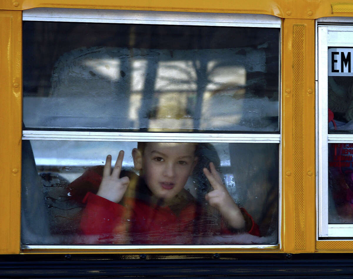 """A Sandy Hook Elementary student flashes a sign as children leave on a school bus in Newtown, Connecticut on January 3, 2013. Students at the elementary school where a gunman massacred 26 children and teachers last month were returning Thursday to classes at an alternative campus described by police as """"the safest school in America."""" Survivors were finally to start their new academic year in the nearby town of Monroe, where a disused middle school has been converted and renamed from its original Chalk Hill to Sandy Hook."""