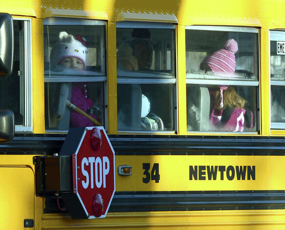 "A Sandy Hook Elementary student looks out the window as children leave on a school bus in Newtown, Connecticut on January 3, 2013.  Students at the elementary school where a gunman massacred 26 children and teachers last month were returning Thursday to classes at an alternative campus described by police as ""the safest school in America."" Survivors were finally to start their new academic year in the nearby town of Monroe, where a disused middle school has been converted and renamed from its original Chalk Hill to Sandy Hook. Photo: TIMOTHY A. CLARY, AFP/Getty Images / 2013 AFP"