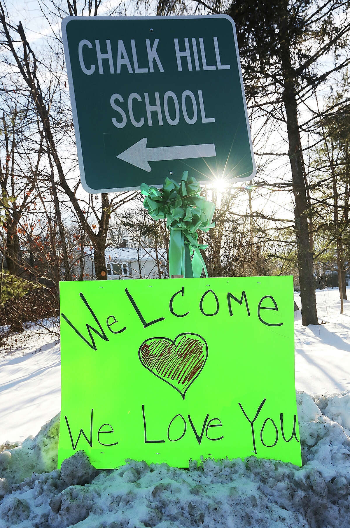 A sign reads 'Welcome We Love You' beneath a sign pointing to the location of Chalk Hill School, which has been refurbished and renamed Sandy Hook Elementary School on January 3, 2013 in Monroe, Connecticut. Sandy Hook students started their first day of classes in the new building following the mass shooting at the old school in Newtown that left 20 students and six faculty members dead.