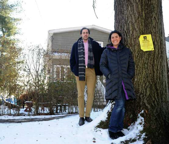 Michelle Lesser and her husband, Zach, pose for a photo outside their home on Ogden Road in Stamford on Thursday, January 3, 2013. Dozens of trees lining the street are scheduled to be removed to enable sidewalk installation. Photo: Lindsay Perry / Stamford Advocate
