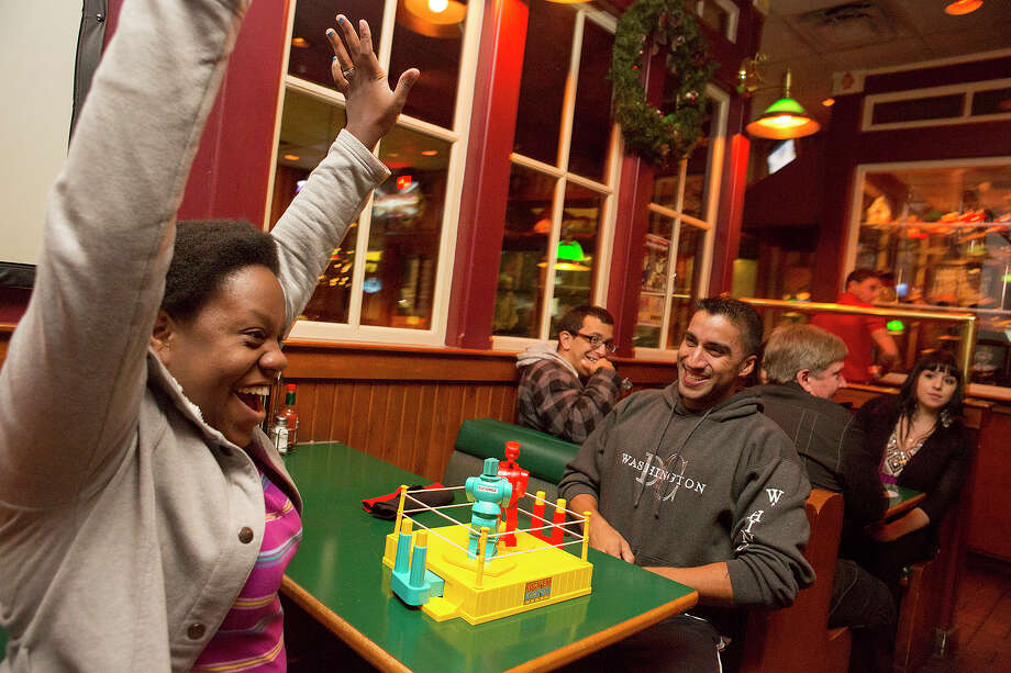 FOR SA LIFE - Farelle Paternella, left, celebrates after defeating JD Barbera in a game of Rock 'Em Sock 'Em Robots during trivia hosted by Geeks Who Drink at the Firehouse Pub & Grill on Wednesday, Dec. 26, 2012. MICHAEL MILLER / FOR THE EXPRESS-NEWS Photo: Michael Miller, San Antonio Express-News / San Antonio Express-News