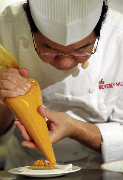 Beverly Hilton executive chef Suki Sugiura prepares a dish during the menu preview on Thursday.