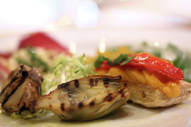 The appetizer dish of grilled artichoke with fennel tomato lemon mousse and California pepper honey goat cheese on endive pear salad. Photo: Matt Sayles/Invision/AP