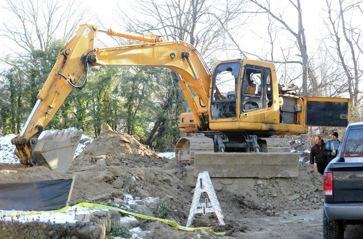 Two men inspect a fire-damaged excavator at 86 Lockwood Road in Riverside, Thursday afternoon, Jan. 3, 2013. Police and fire investigators are trying to figure out how the excavator caught fire late Wednesday night.