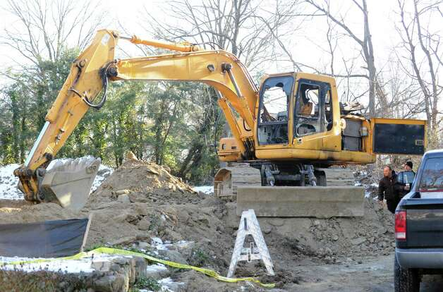 Two men inspect a fire-damaged excavator at 86 Lockwood Road in Riverside, Thursday afternoon, Jan. 3, 2013. Police and fire investigators are trying to figure out how the excavator caught fire late Wednesday night. Photo: Bob Luckey / Greenwich Time