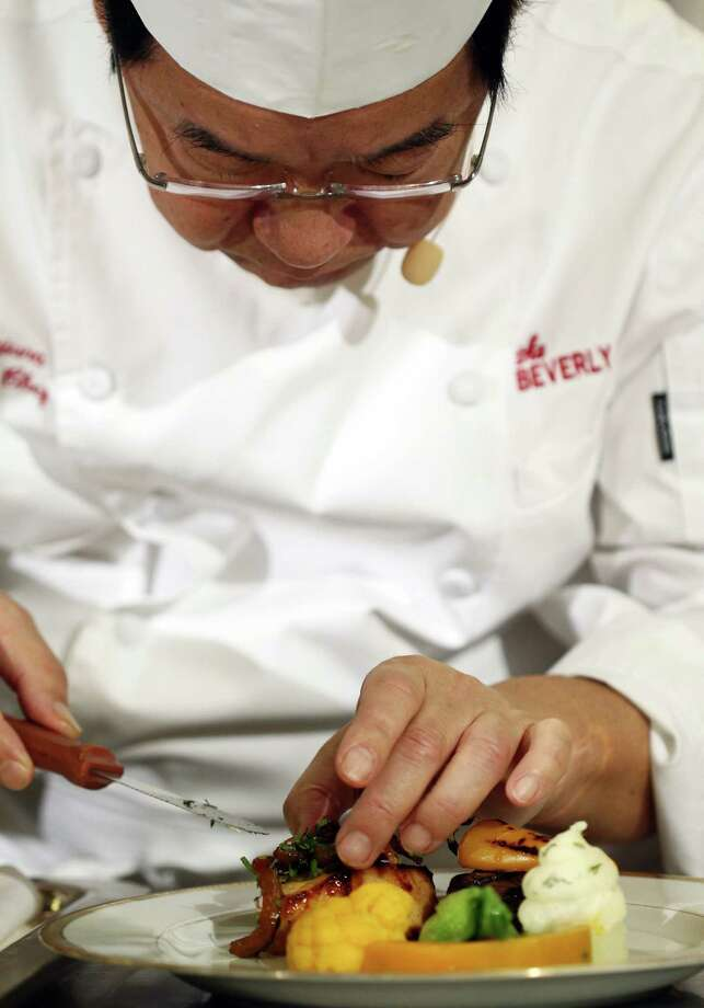 Beverly Hilton executive chef Suki Sugiura prepares the entree dish during the menu preview. Photo: Matt Sayles, Associated Press / Invision