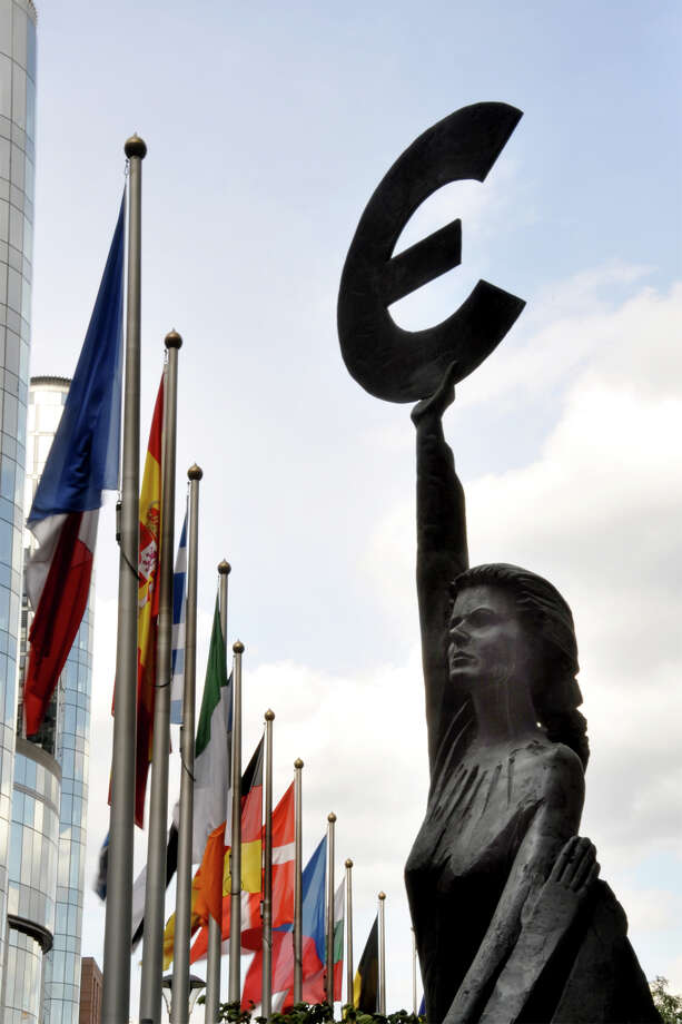 This statue, just outside the European Parliament in Brussels, holds the symbol of the euro — Europe's common currency. Photo: Cameron Hewitt, Ricksteves.com
