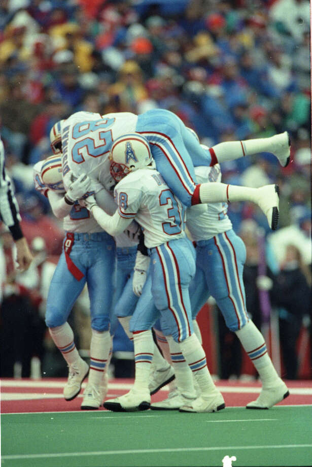 Oilers players mob Bubba McDowell after his third-quarter interception return for a touchdown in the AFC wildcard game against the Buffalo Bills.