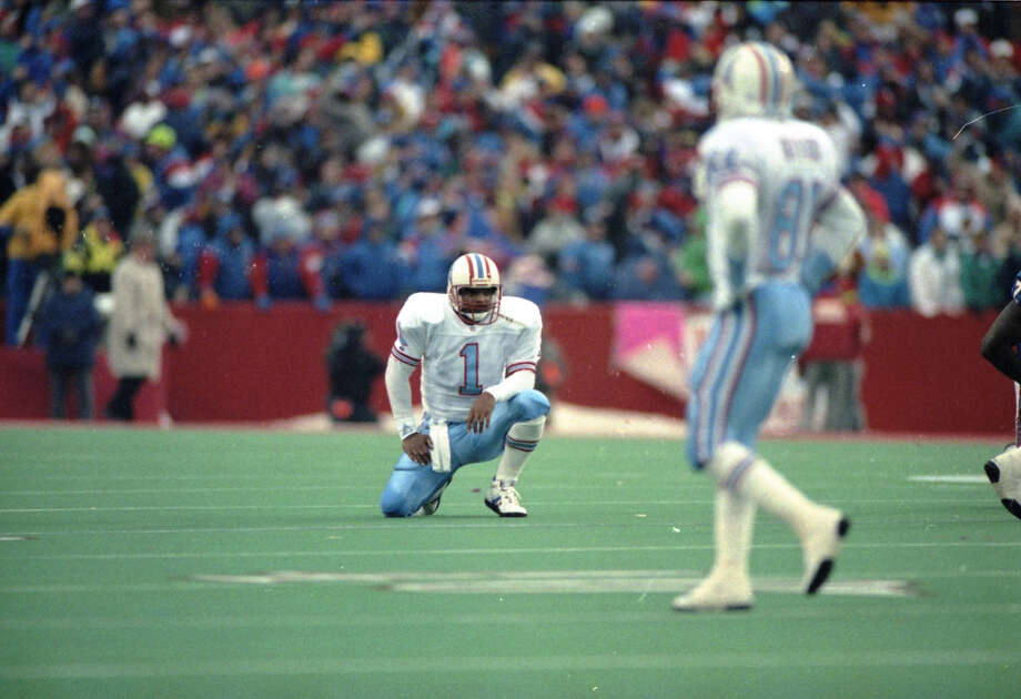 Oilers quarterback Warren Moon sits on the turf after throwing an interception in the third quarter